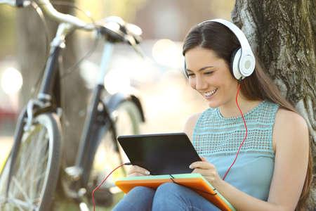 행복 한 학생 공원에 앉아 태블릿에서 줄에 미디어 콘텐츠를보고 스톡 콘텐츠