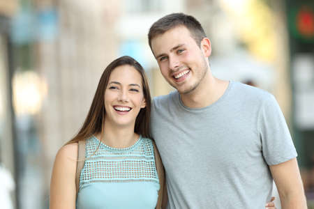 Front view portrait of a happy couple walking together on the street