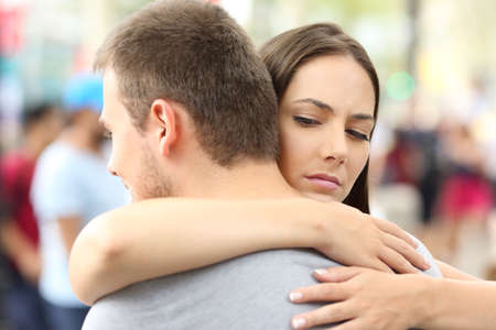 Discontent girlfriend hugging her partner on the street Standard-Bild