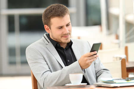 mobile app: Serious executive using a mobile phone sitting in a coffee shop Stock Photo