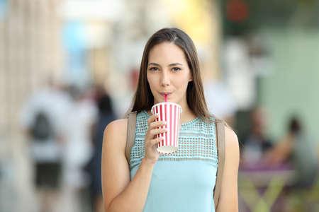 bebes lindos: Vista frontal de una chica bebiendo una bebida para llevar caminando por la calle Foto de archivo