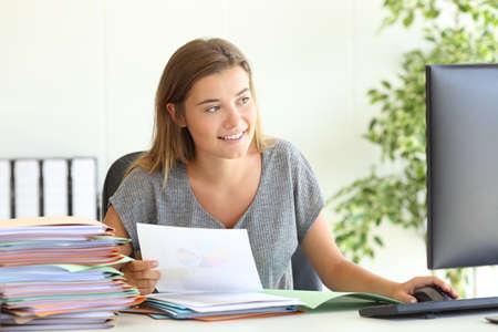 사무실에서 책상에 앉아있는 컴퓨터와 온라인으로 보고서를 비교하는 행복한 직원의 전면 모습 스톡 콘텐츠