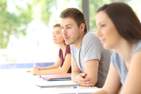 uninterested: Distracted student looking away during a class at classroom