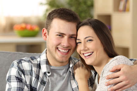 Happy couple with perfect teeth looking at camera sitting on a couch at home Stock Photo