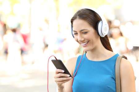 Portrait of a girl listening to music wearing headphones and walking on the street