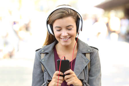 Front view of a smiling teen listening to music on a smart phone on the street