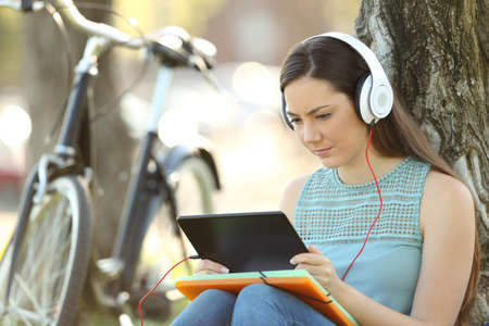 Student e-learning with a tablet and headphones sitting outdoors in a park Reklamní fotografie