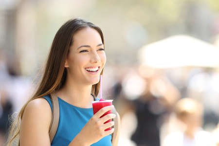 Single happy woman walking and holding a slush in the street