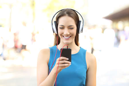 Front view portrait of a girl listening to music on a phone wearing headphones on the street