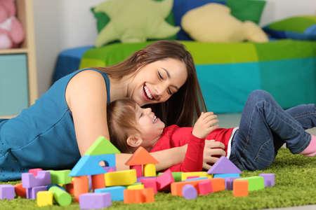 집에서 방에있는 카펫에 아이와 놀고있는 어머니 또는 보모 스톡 콘텐츠