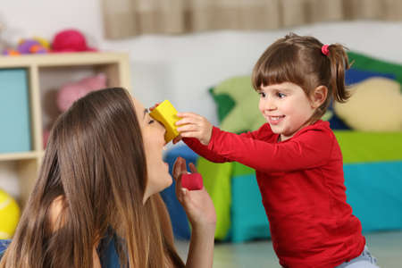 babysit: Happy daughter playing with her mother on the floor of a room at home Stock Photo