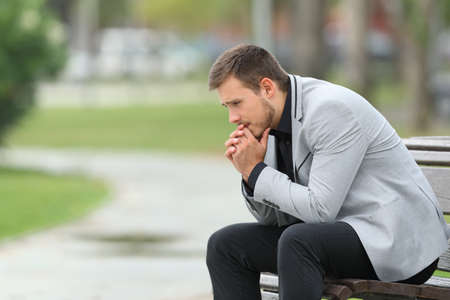 Side view portrait of a worried businessman sitting on a bench in a park