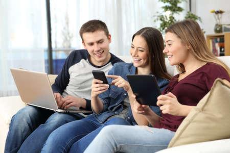 Drie gelukkige vrienden die online inhoud met veelvoudige apparaten delen die op een bank thuis zitten