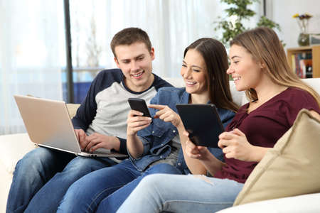Three happy friends sharing on line content with multiple devices sitting on a sofa at home Banque d'images