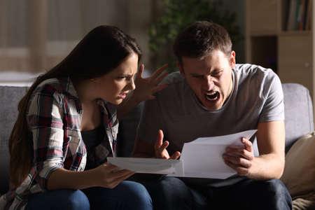 Woedend paar dat een brievenzitting op een laag thuis leest Stockfoto