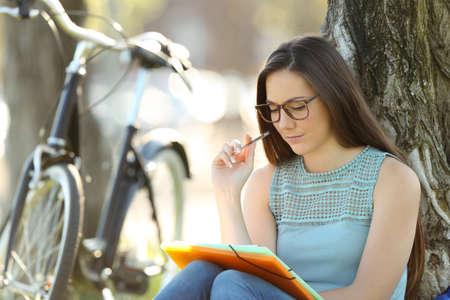 Single student wearing eyeglasses memorizing notes sitting in a park Stock Photo