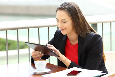 Happy executive working with a tablet sitting in a coffee shop