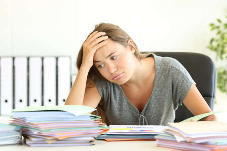 Portrait of an overworked employee tired looking at a lot of documents on a desktop at office Stock Photo