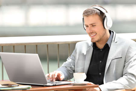 Portrait of an executive wearing headphones working on line sitting in a coffee shop Фото со стока