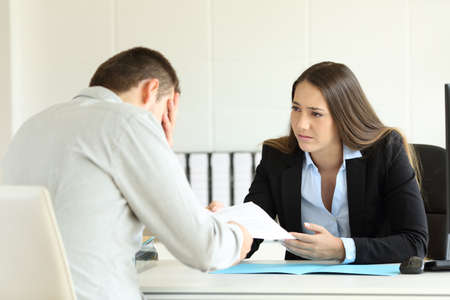Sad boss firing an employee sitting in her desktop at office Stock Photo - 84357253
