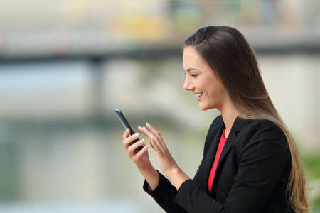 Profile of an executive using a smart phone outside on the street Stock Photo