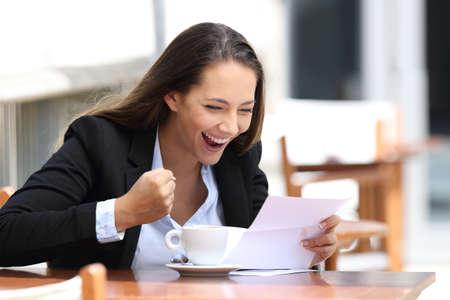 Eccitato businesswoman che legge una lettera seduto in un caffè all & # 39 ; aperto Archivio Fotografico - 84357255