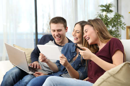 Three happy friends laughing hard watching videos sitting on a couch at home