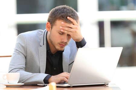 Retrato de un ejecutivo preocupado trabajando en línea sentado en una cafetería Foto de archivo - 84357287