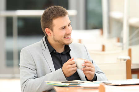 positivismo: Portrait of a pensive executive looking away sitting in a coffee shop Foto de archivo