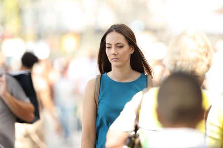 Droevige vrouw die alleen het lopen tussen mensen op de straat voelen