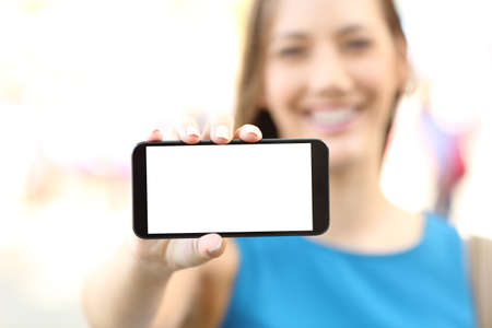 Close up of a happy female showing a blank horizontal phone screen on the street Фото со стока