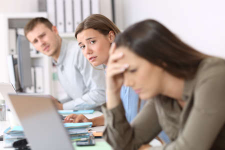 Sad workers looking at a frustrated colleague who is reading bad news on line at office Stock Photo