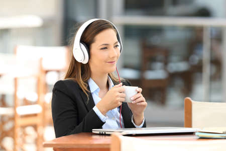 Portrait of a pensive businesswoman listening music and holding a coffee cup sitting in a bar