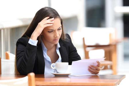 Bezorgd stafmedewerker die een briefzitting in een koffiewinkel leest