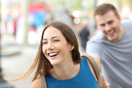 Funny couple of teenagers running towards camera on the street photo
