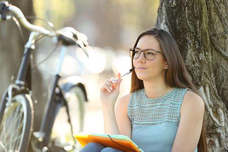 Étudiant célibataire pensant et regardant le côté assis dans un parc Banque d'images