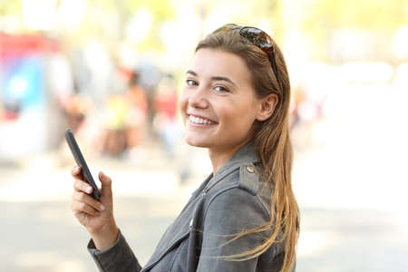 Happy teen with mobile phone looking at camera on the street