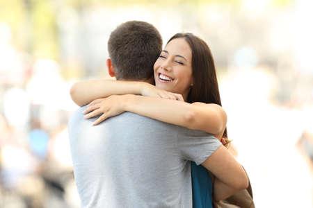 길거리에서 만난 후 그녀의 파트너를 포옹하는 행복 한 여자 친구