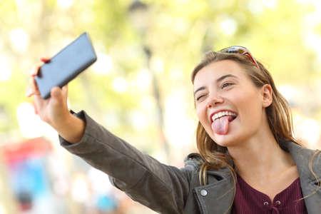 Portret van een grappige tiener die selfies en grimacing op straat neemt