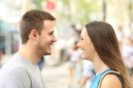 love at first sight: Profile of couple looking each other falling in love on the street