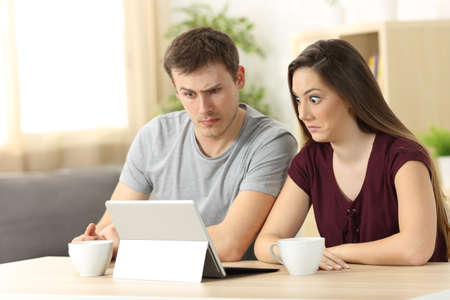 Confused couple receiving on line news sitting in a desk at home photo
