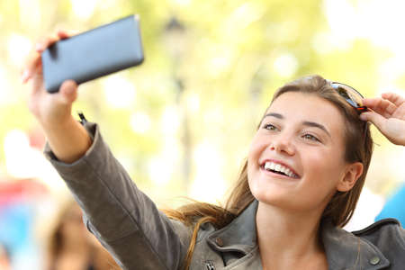 Fashion teen taking selfies with a smart phone on the street