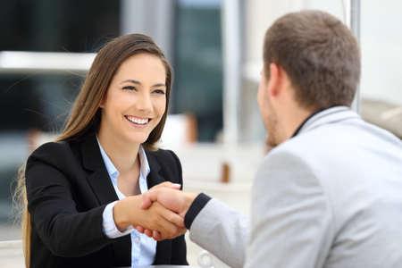 Due dirigenti riunione e handshaking seduto in un negozio di caffè
