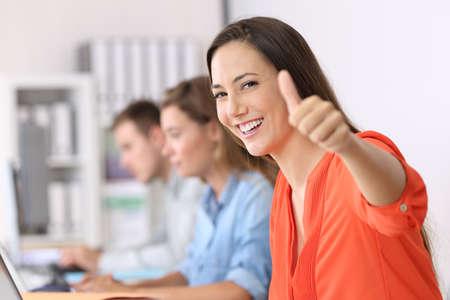 Retrato de un empleado feliz que le mira con los pulgares para arriba que se sienta en una mesa en la oficina Foto de archivo - 85485824