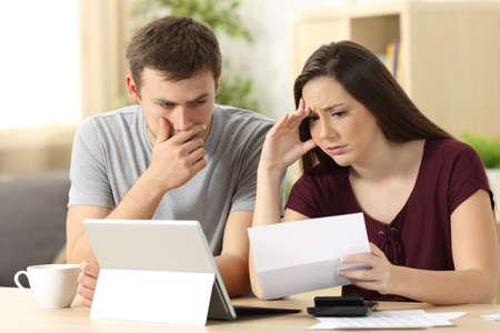 Besorgte Paare, die zusammen einen Brief zu Hause sitzen in einem Schreibtisch lesen Standard-Bild - 85485827