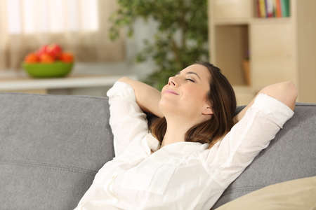 Happy homeowner relaxing alone sitting on a couch at home