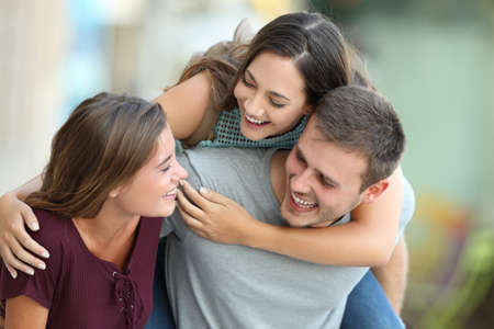 positivism: Three happy friends meeting and joking together on the street Stock Photo