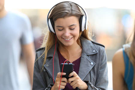 Front view portrait of a happy girl listening to music wearing headphones and walking on the street