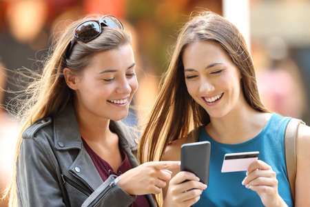 Twee gelukkige vrienden die online met creditcard en slimme telefoon op straat kopen Stockfoto - 84651464