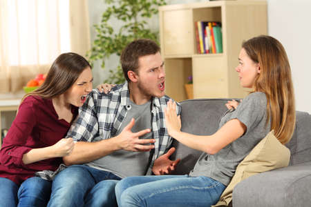 envious: Roommates arguing and shouting each other on a sofa at home Stock Photo